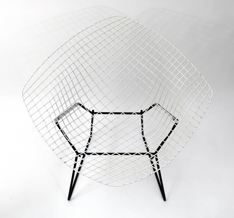 'Diamond' chair designed by Harry Bertoia for Knoll, in white enameled stainless steel on a welded black steel base.  Please note: Pickup for this chair is in Denver, CO.  The diamond chair is, according to Knoll, an astounding study in space,