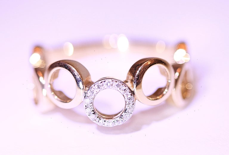 A diamond band made with 7 circles and one has pave' diamonds on top.  The band has  .07 carat total weight of tiny round brilliant cut diamonds.  The band can be used as a  wedding band or a right hand ring.  The band is a size 6 3/4 and it can be