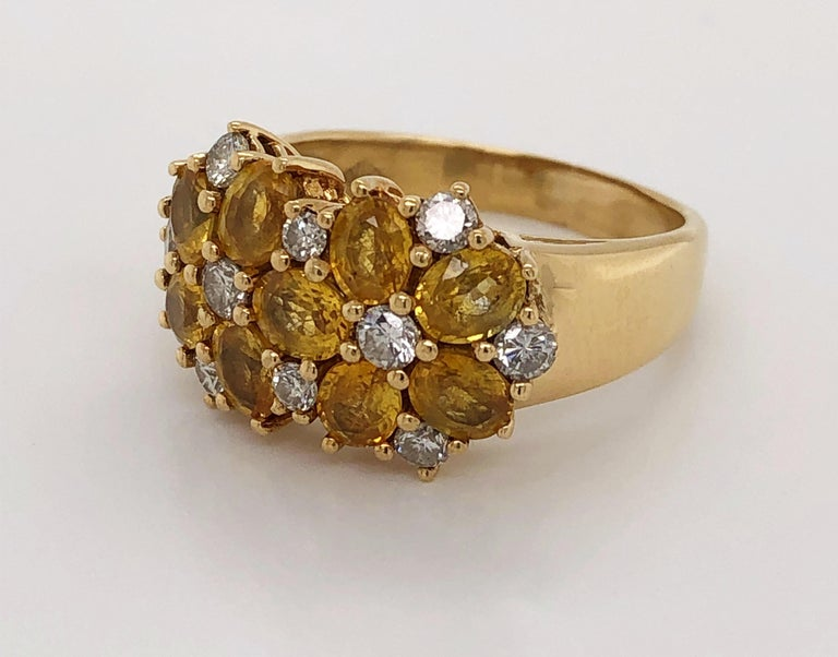 Radiant combination of sunny citrine gemstones and bright white diamonds create this cheerful cluster cocktail ring. With a graduated band in eighteen karat 18K yellow gold, the dazzling floral cluster head, measuring approximately 12.8 mm H x 19 mm