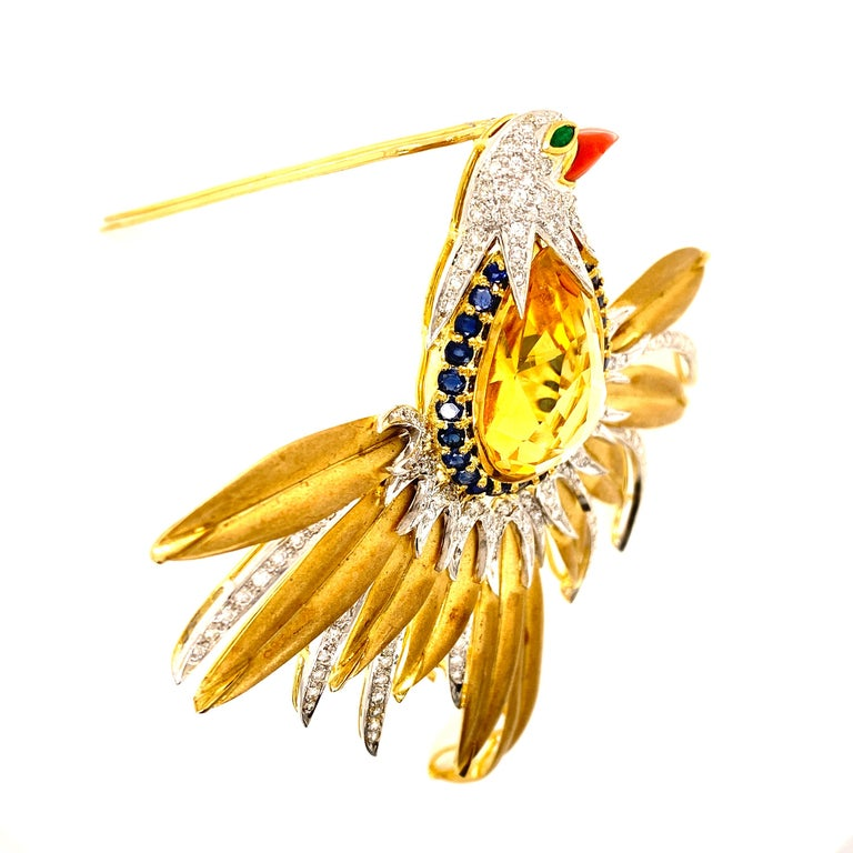 Big and Colorful Bird Brooch fashioned in 18 karat yellow gold. This piece of art features a 26.75 carat faceted citrine gemstone as the body of the bird surrounded by sapphires, diamonds, emerald, and coral accents. The wings span 3.5 inches in