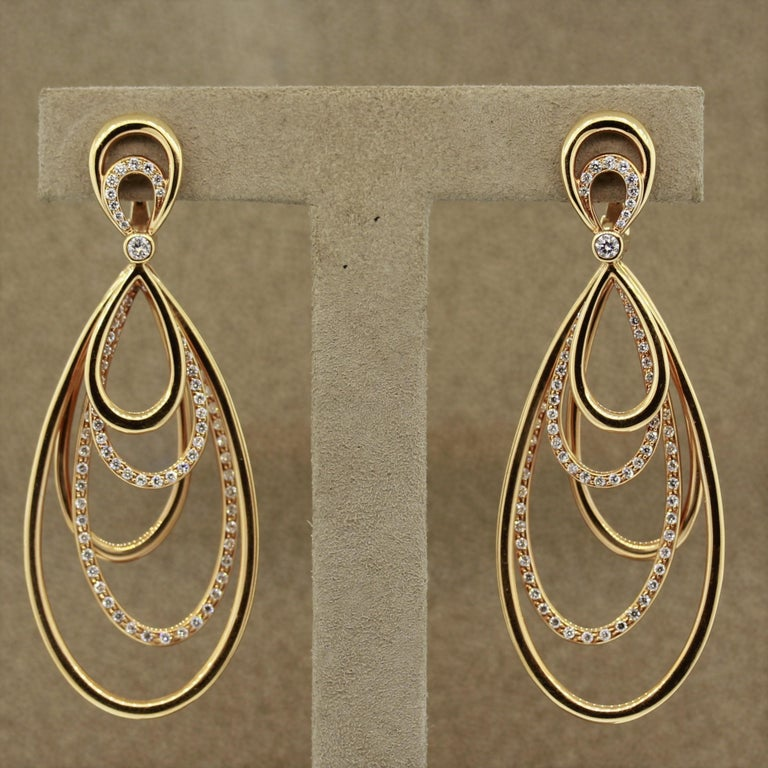 A lovely pair of earrings featuring multiple gold loops which dangle independently from one another. They are set with 1.92 carats of round brilliant cut diamonds along with a larger diamond in the center. Made in 18k rose gold, these earrings will
