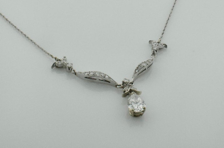 Diamond Dangling Pear Shape Necklace in Platinum on 14k Chain c. 1950's One Pear Shape Diamond Weighing 1.21 GIA Certified G I1 [bright with no imperfections visible to the naked eye] Seventeen Round Cut Diamonds weighing .45 carats approximately