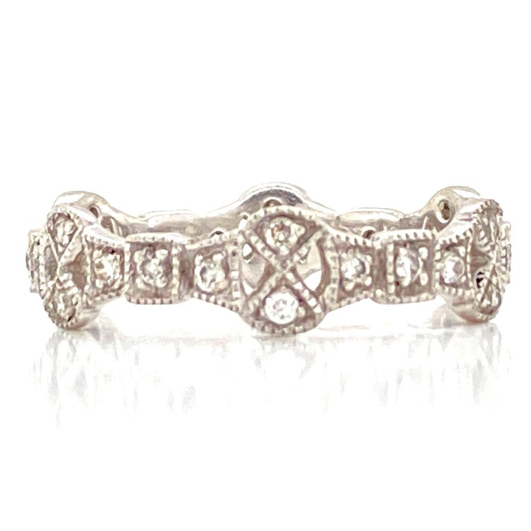 Diamond filigree Deco style eternity band crafted in platinum. The band features .30 carat total weight of round brilliant cut diamonds graded H-I color and SI clarity.  The band is size 7 and measures approximately 5mm in width.