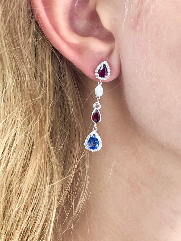 Fourteen karat white gold drop earrings two inch long Diamonds weighing 1.25 carat  Pear shape rubies weighing 2.01  carat Pear shape sapphires weighing 1.70 carat One of a kind earring New Earrings Handmade in the USA Our team of graduate