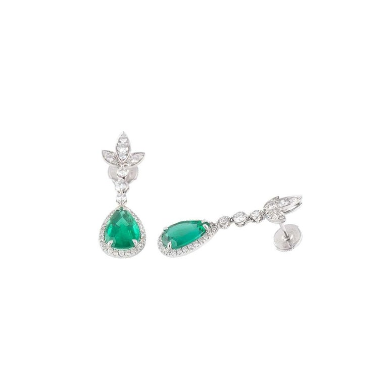 A stunning 18k white gold diamond and emerald drop earrings. The earrings each comprise of 3 conjoined marquise shapes with round brilliant cut diamonds set in them with 3 round brilliant cut diamonds dangling vertically in a column with a pear