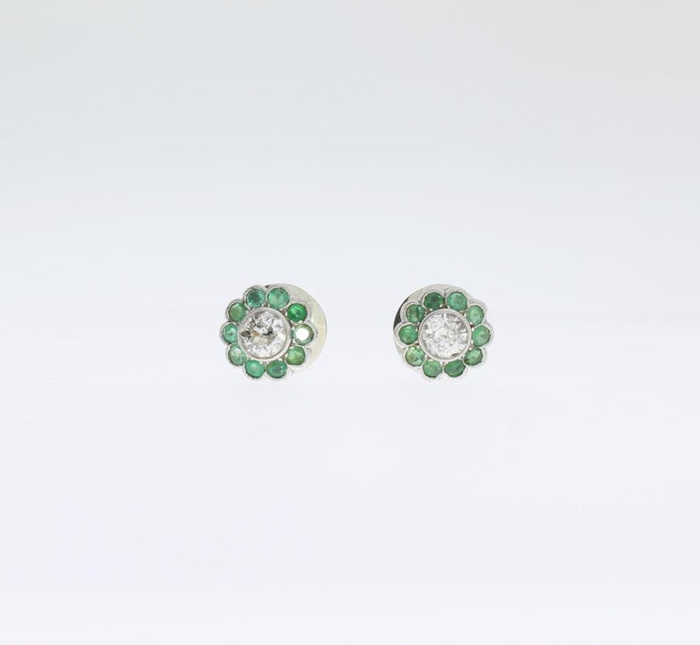 These emerald and diamond studs are designed in a floral shape, circa 1960's. With 2 brilliant-cut diamonds weighing approximately 1,20 ct. Clarity: pique. Surrounded by 20 nature emeralds with a total weight of circa 1,0 ct. Mounted in white gold.