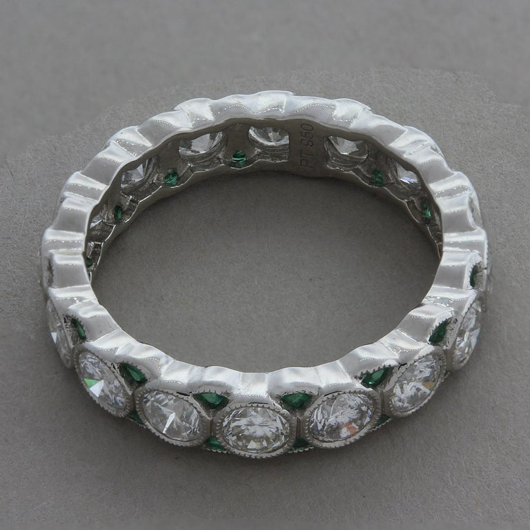 A classic diamond eternity band with emerald accents. Their lovely ring features 3.08 carats of round brilliant cut diamonds with small emerald accents between the diamonds. The diamonds are bezel set in platinum with a classic milgrain