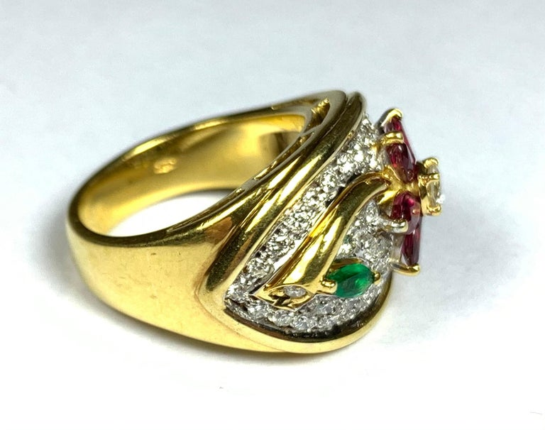 A striking 18ct yellow gold ring designed as a flower, set with diamonds, rubies and an emerald. Can be sized. Ring size 5 1/8.