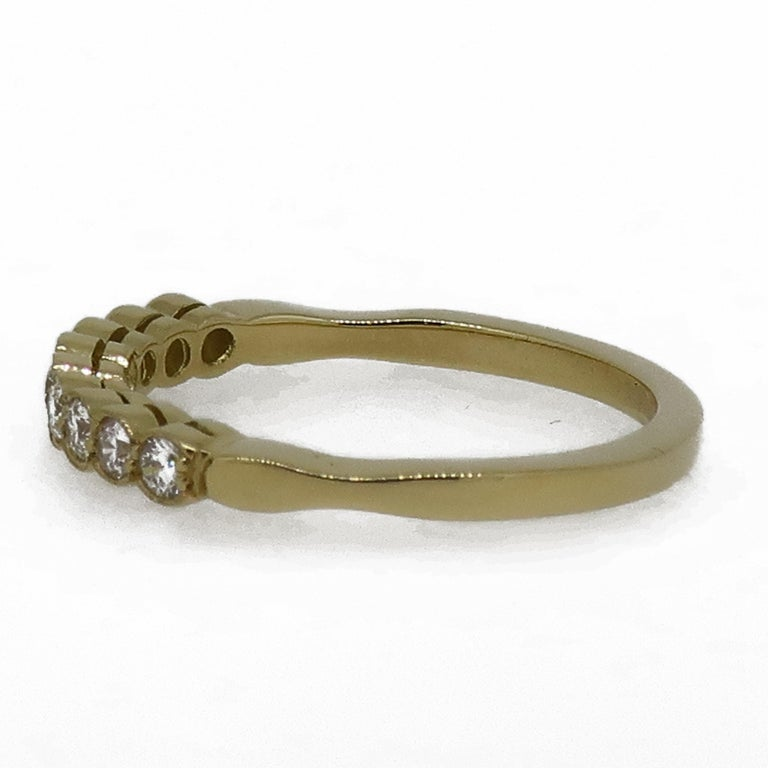Diamond Eternity Band Ring 18 Karat Yellow Gold  A dainty diamond eternity ring. Consisting of nine white brilliant cut diamonds, weighing 0.30ct in total. All set in a delicate mill-grain setting in 18 carat yellow gold. It would make the perfect