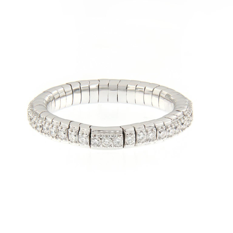 This beautiful flexible diamond band ring is designed for comfort and perfectly fits one's finger. Ring is crafted in 18k white gold. Band can stretch up to 1.5 in size. The ring is great for stacking and would complement an engagement ring. Ring