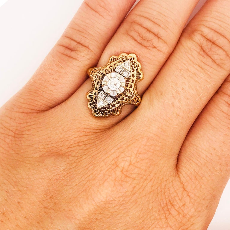 The 1930's were romantic, classy and decorative. The 1920-30 time period is well known for its fashion trends and Art Deco design. This ring embodies the true Art Deco 1930's perfectly. This filigree, diamond dinner ring has an open filigree design