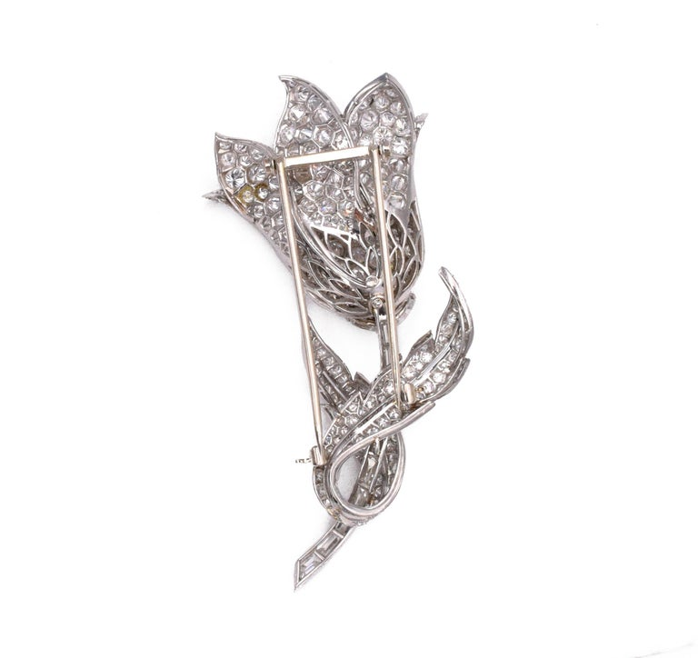 Platinum and Diamond Flower Clip- Brooch The stylized tulip with overlapping petals and leaves pavé-set with round diamonds, completed by a stem of baguette and fancy-shaped diamonds, altogether approximately 17.15 cts.,   Measuring 3 x 1 3/8 inches.