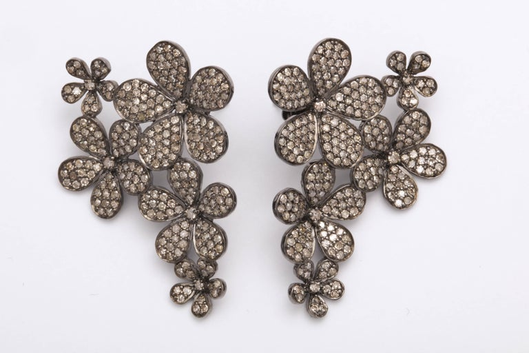 A fun and fashionable pair of diamond earrings.   3.65 carats of round brilliant cut diamonds set in silver with gold posts and backings.  Just over an inch at its widest point, 1.57 inches long.  A BEAUTIFUL GIFT!