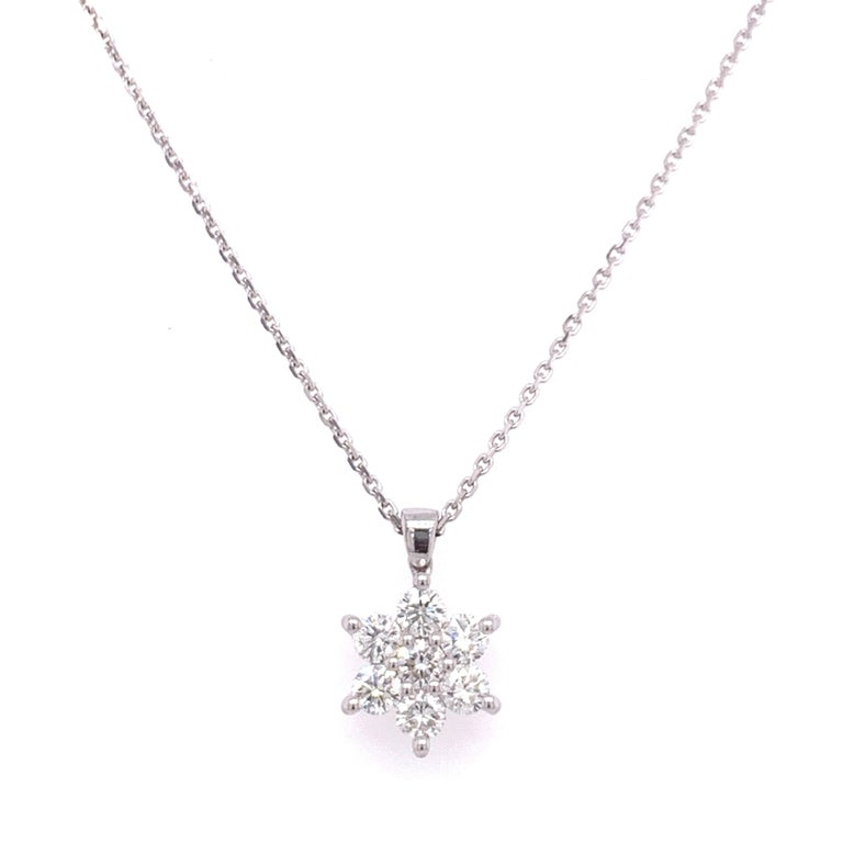 Flower shaped diamond pendant necklace made with natural/brilliant cut diamonds. Total Diamond Weight: 0.60 carats. Diamond Quantity: 7 round diamonds. Color: G. Clarity: SI. Mounted on 18 karat gold adjustable chain.