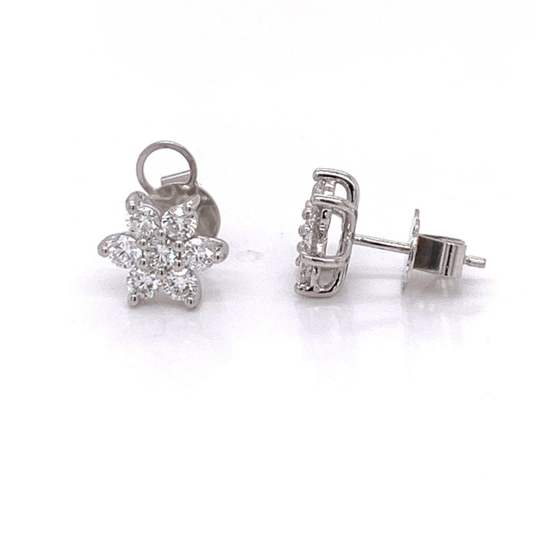 Flower shaped diamond stud earrings made with real/natural brilliant cut diamonds. Total Diamond Weight: 1.14 carats. Diamond Quantity: 14 round diamonds. Color: G. Clarity: VS. Mounted on 18 karat gold pushback setting.