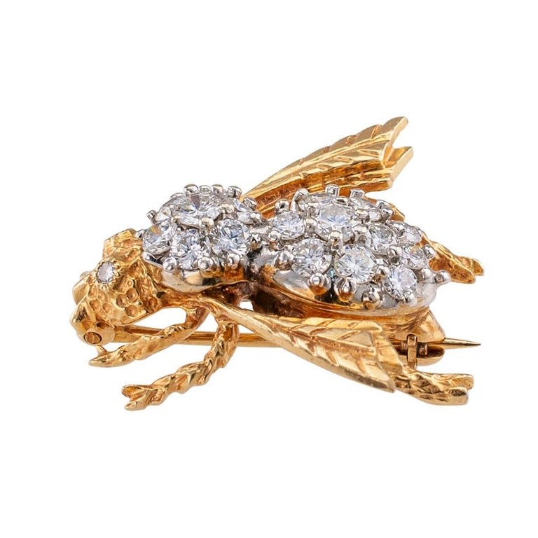 Diamond and gold bee brooch circa 1980. The honeybee brooch has diamond-set eyes, its body set with more diamonds and the head, legs and wings in yellow gold decorated with organic motifs relevant to a bee's body, the diamonds totaling approximately