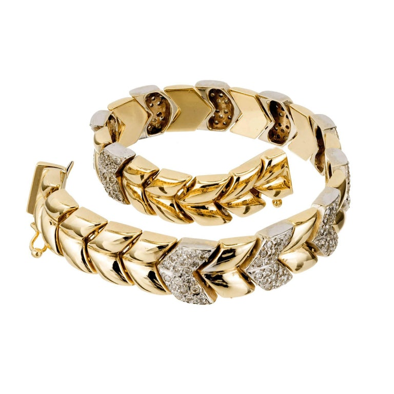 Chevron link solid 14k yellow gold 3/8 inch wide hinged bracelet with white pave set diamond sections set with full cut diamonds. Circa 1960-1970. Built in catch and side lock safety.  180 full cut diamonds approx. total weight 2.50cts, H,