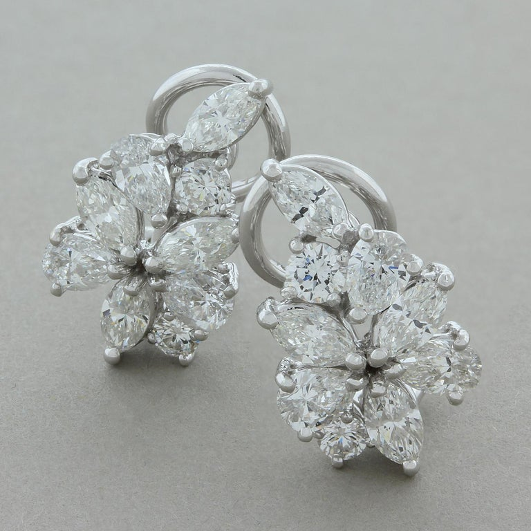 These cute flower cluster earrings feature 3.40 carats of diamonds, marquise, pear and round brilliant cut. The cluster is set in 18K white gold with an omega backing.   Earring Length: 0.50 inches Earring Width: 0.25 inches