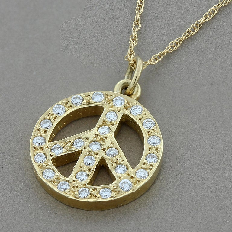 A classic peace sign pendant featuring 0.20 carats of diamonds. Set in 14K yellow gold. Peace out!  Chain Length: 18 inches  Pendant Length: 5/8 inch  Pendant Width: ½ inch