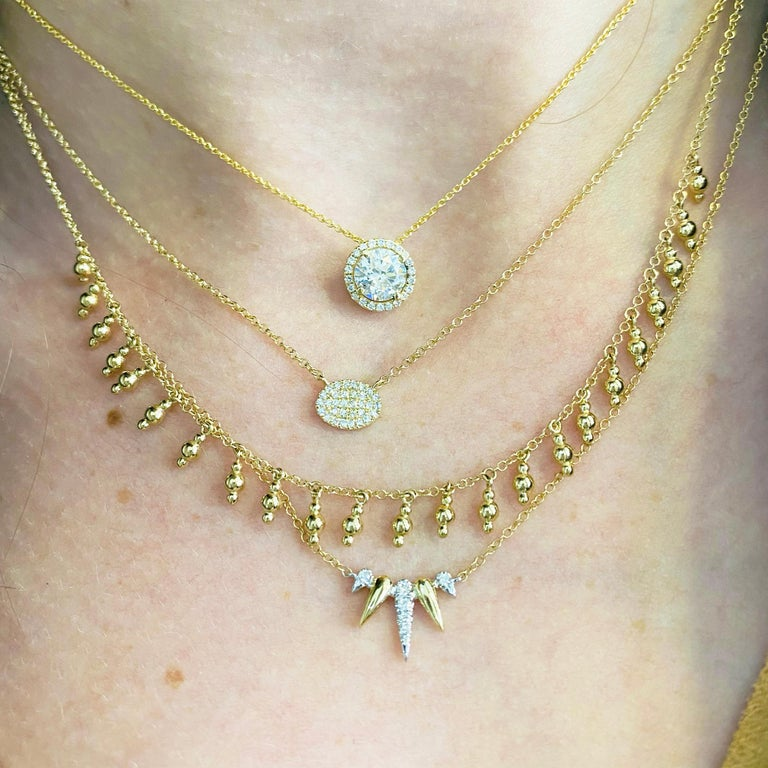 This gorgeous .94 carat center diamond set inside a brilliant white diamond halo and delicately hanging from a 14k yellow gold chain is sure to put a smile on anyone's face! The adjustable chain with an adorable hidden heart design on this necklace