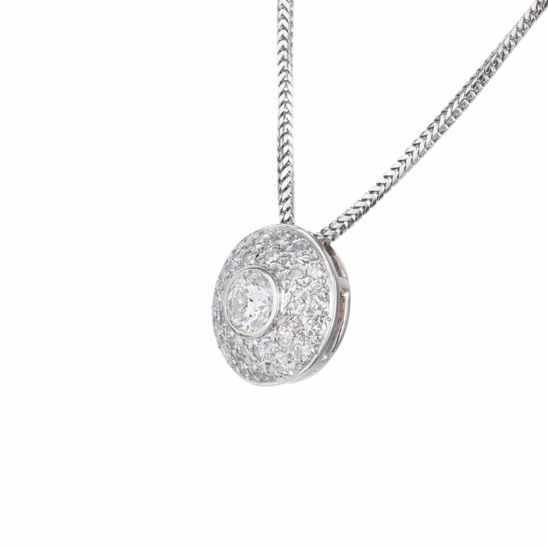 Diamond domed pendant necklace. .53ct center bezel set diamond with a halo of 25 pave set diamonds in 14k white gold. 18 inch snake style chain.   1 round diamond approx. total weight .53ct, G, SI1. 25 round diamonds approx. total weight .46cts, G,