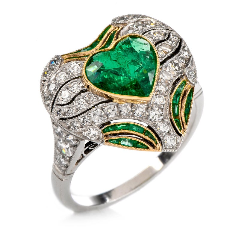 This timeless heart shaped emerald and diamond ring is crafted in a combination of solid platinum and yellow gold. Composed of a heart shaped frame pave-set with round-cut diamonds weighing approx. 1.70 carats, graded H-I color, and VS clarity.