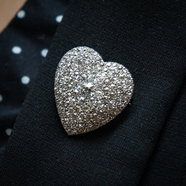 An Art Deco diamond heart pendant/ brooch, pavé set with graduating old cut diamonds, with an estimated total diamond weight of 6.50ct, mounted in platinum and 18ct yellow gold, with a pendant and brooch fitting. Measures approximately 35 x 30mm.