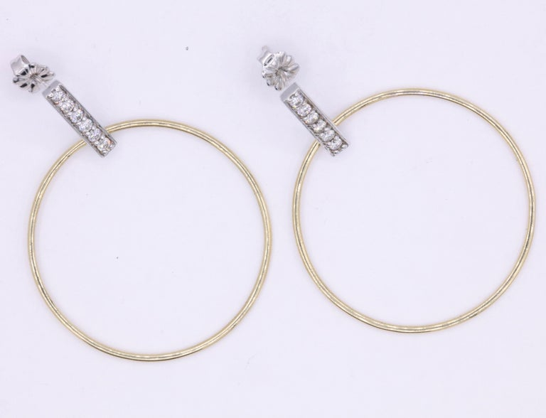 These fun and playful hoop earrings feature a diamond bar with 12 round brilliants weighing 0.33 carats, in 14k white and yellow gold.  Color: G-H Clarity: SI