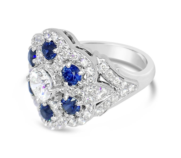 A beautiful and delicate 18 karat white gold ring set with a center diamond of 0.61 carats H color and VS clarity surrounded by 1.22 carats total of blue sapphires and another 0.69 carats total weight of diamond pave.  The ring is a size 6.5 and is