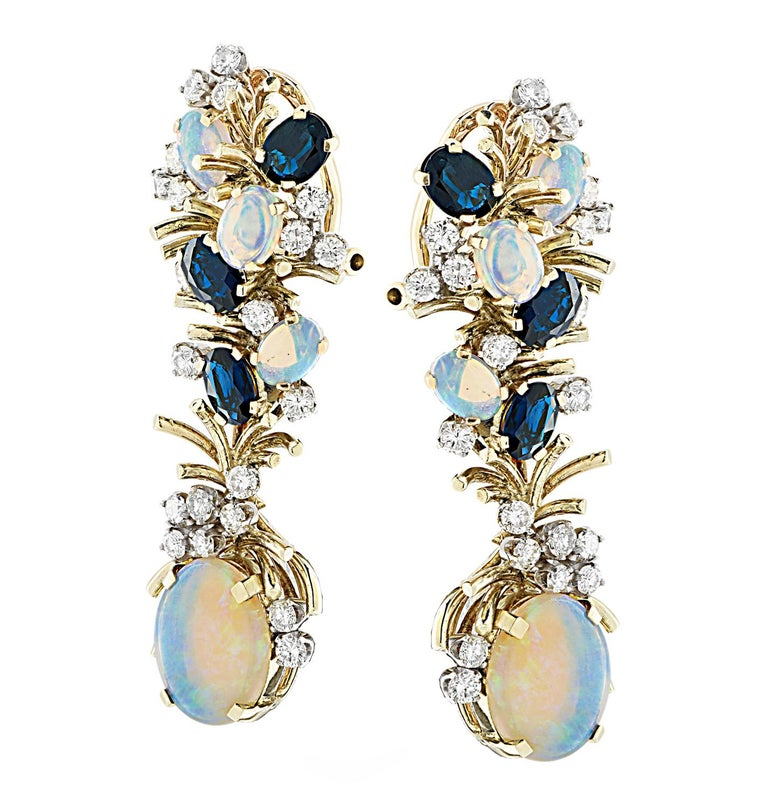 Spectacular dangle earrings crafted in yellow gold, showcasing 8 oval opals weighing approximately 3.5 carats total, 6 oval cut sapphires weighing approximately 1.5 carats total and 42 round brilliant cut diamonds weighing 2 carats total, G-H color,