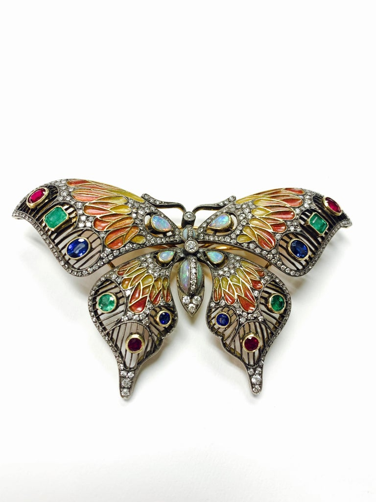 Diamond, opal, emerald, blue sapphire and rubies butterfly broach in 18k and silver.  The details are as follows :  Diamond weight : 3.05 carat  Opal weight : 3.75 carat  Emerald, Blue sapphire , rubies weight : 4.35 carat  Metal : 18 K gold and