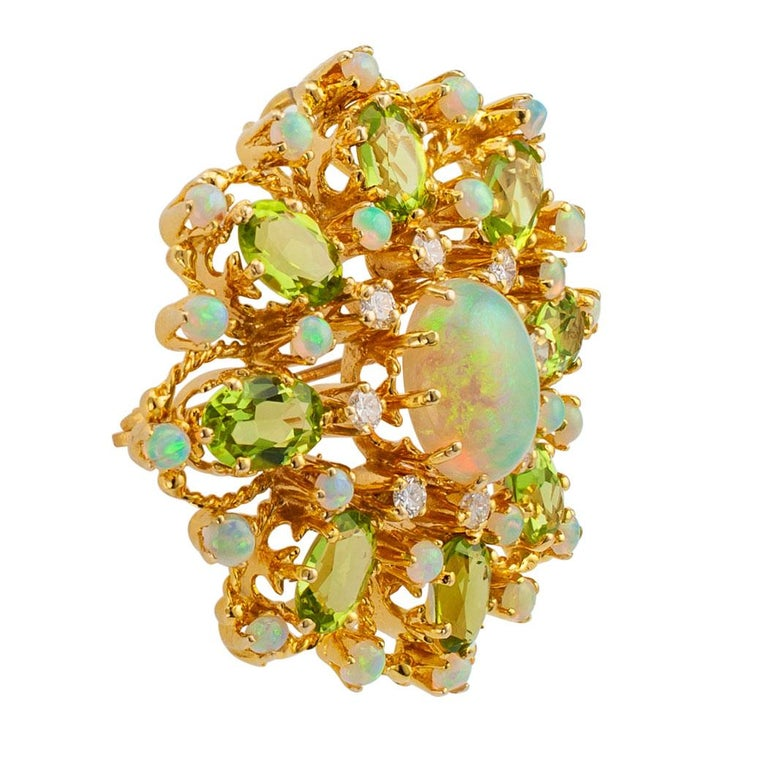 Diamond opal peridot and gold brooch pendant circa 1960. The open work starburst design features a larger oval opal encircled by diamonds, small round opals and oval peridot, the diamonds totaling approximately 0.45 carat, approximately H – I color