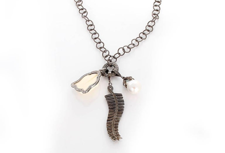 This beautiful bohemian inspired necklace features baroque pearl and feather pendants with an oxen bone Buddha pendant outlined by diamonds on a diamond oval clasp; all set in oxidized sterling silver. Sterling silver chain measures apx. 36-inches