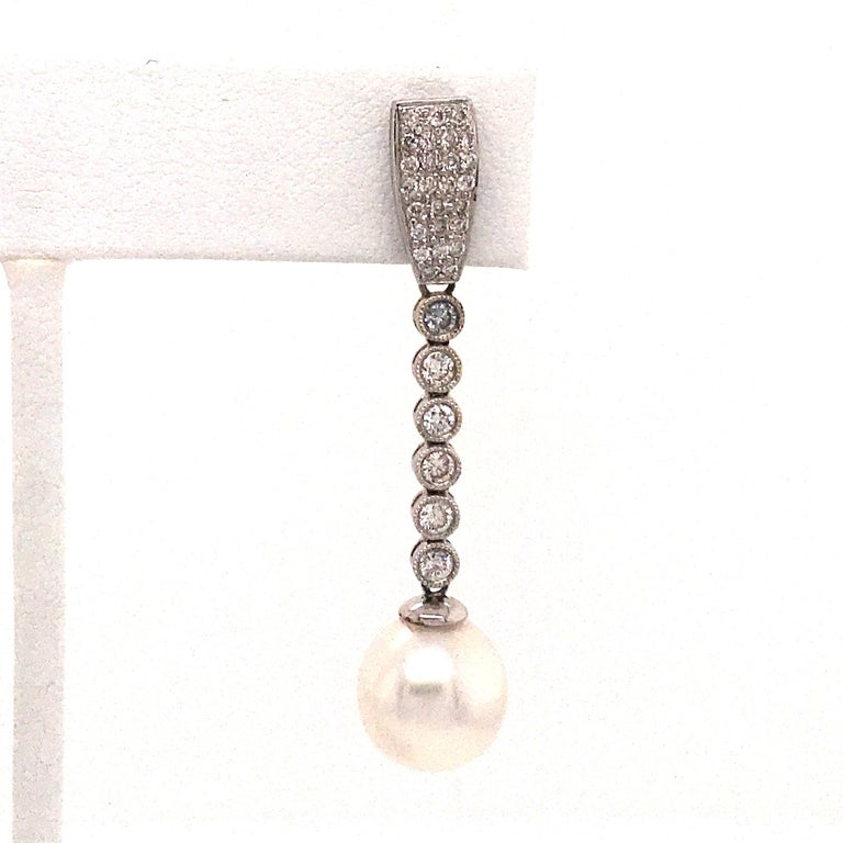 18K White gold earrings featuring two pearls measuring 10-11 mm with a diamond drop weighing 1.50 carats.  Color G-H Clarity SI