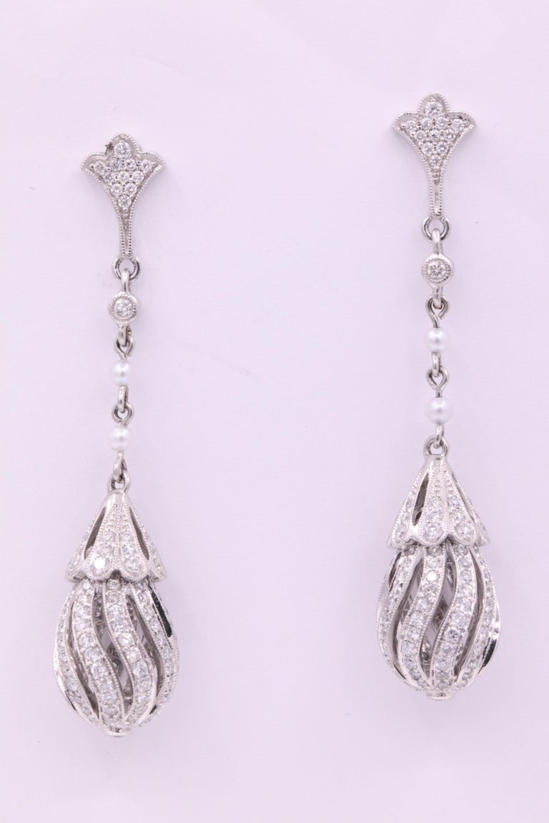 Art Deco style earrings featuring round brilliants weighing 2.71 carats with touches of white pearls, crafted in platinum.  Color G Clarity SI