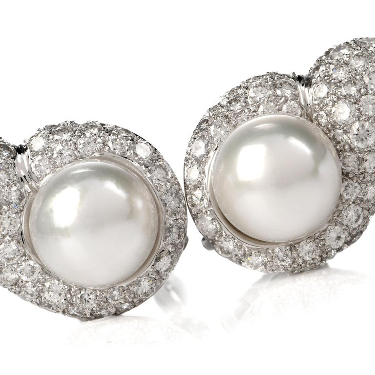 These elegant diamond and pearl tear drop shaped clip on earrings are crafted in solid 18 karat white gold, weighing 23.6 grams and measuring 30mm x 20mm. Showcasing a pair of prominent lustrous cultured pearls in white creamy color and measuring