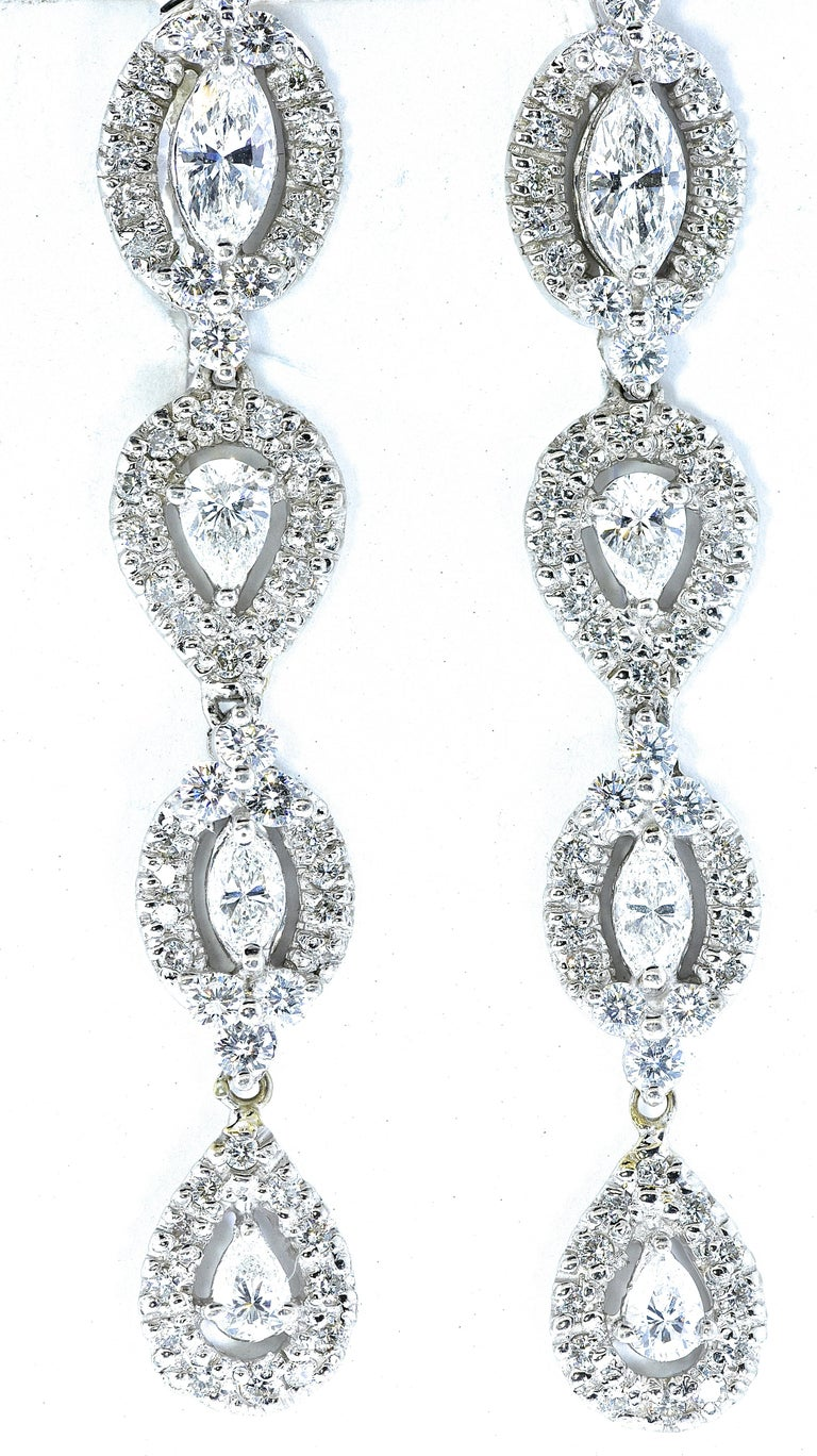 Diamond earrings possess fine white well cut and well matched diamonds -  well cut and very white (G/H,VS).  There are approximately 3.2 cts. of round, pear and marquis cut diamonds set in 18K white gold.  These earrings are two inches long.   They