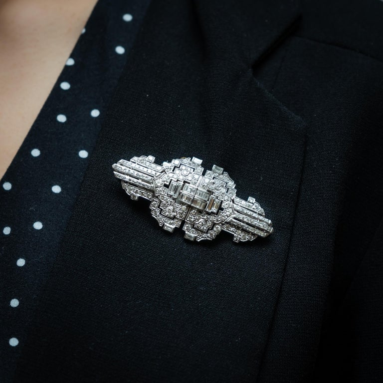 An Art Deco diamond double clip brooch, set with approximately 7.00ct of round brilliant-cut and baguette-cut diamonds, mounted in platinum with white gold fittings, measuring approximately 6.2 x 2.7cm, circa 1930.