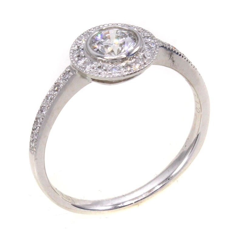 Beautifully designed and masterfully handcrafted in platinum, this perfect engagement ring features a centrally bezel set round brilliant cut diamond weighing 0.41 carats. Surrounding this diamond is a halo of bright white round brilliant cut
