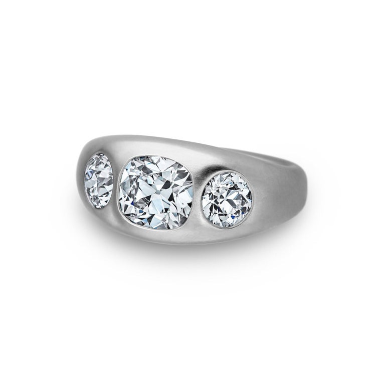 It's a triple header! With two scintillating old euro round cut diamonds surrounding one cushion brilliant cut center diamond, this handmade three stone matte finished platinum gypsy ring is a grand slam.  Designed by Steven Fox Jewelry.  Weight of