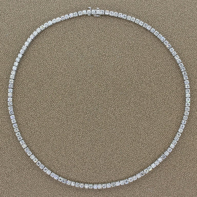 A classic tennis necklace featuring 12.90 carats of diamonds. The colorless round cut diamonds are prong set in luxurious platinum. A seamless closure is provided by a hidden safety latch for safe keeping.   Necklace Length: 15.00 inches  Necklace