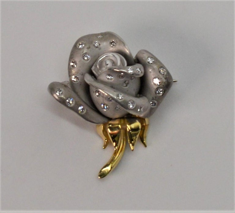 Petite floral bud pin brooch made of satin finished platinum with sparkling diamond accents complimented by a yellow gold stem & leaves. This cheerful piece measures approximately 3/4 inch and has just the right amount of classic detail. In gift