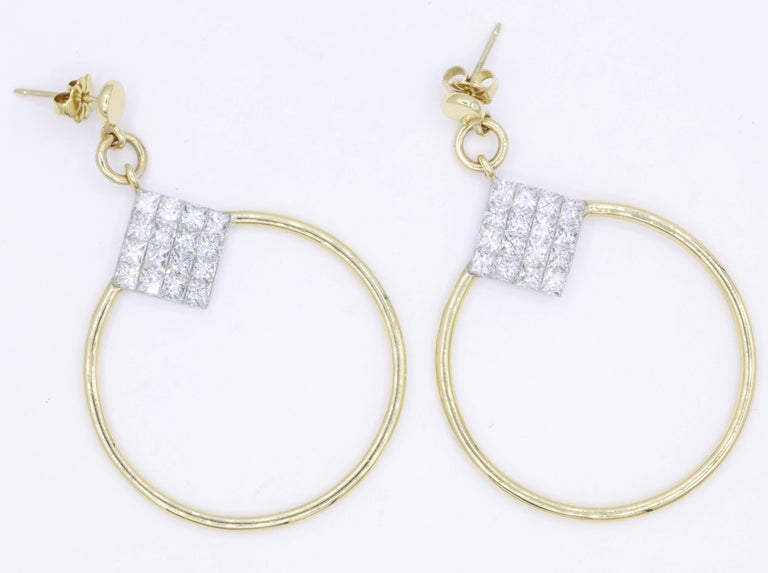 These 18K yellow gold hoop earrings feature 32 princess cut diamonds weighing 4 carats. Greats great on the ear!! Color: G-H Clarity: SI