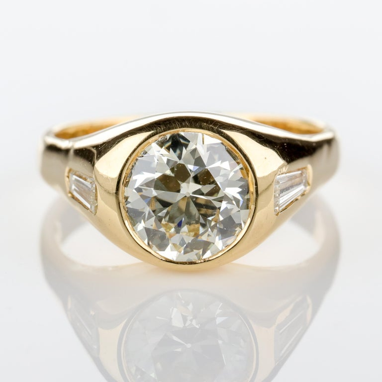 This vintage—circa 1960's—18k yellow gold ring features a firey 2-carat old European-cut diamond of excellent color (L-M) and clarity (VS). Two 4.4 mm x 2.3 mm tapered baguette diamonds sharpen the shoulders. This is a beautifully-cut old diamond