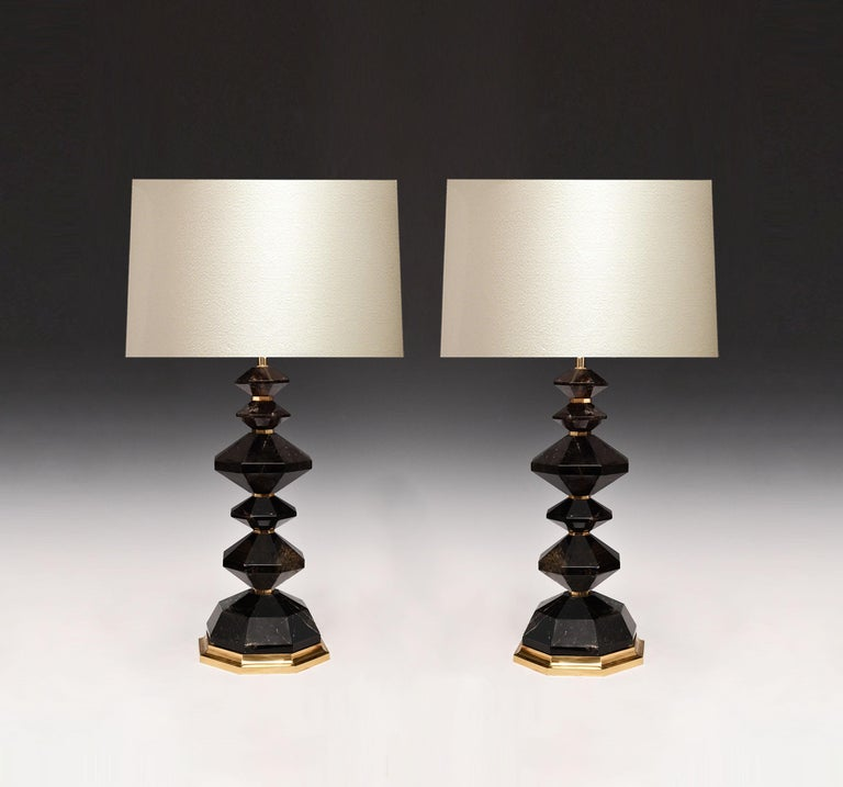 A pair of carved dark diamond rock crystal lamps with polish brass decoration. Created by Phoenix Gallery, NYC.