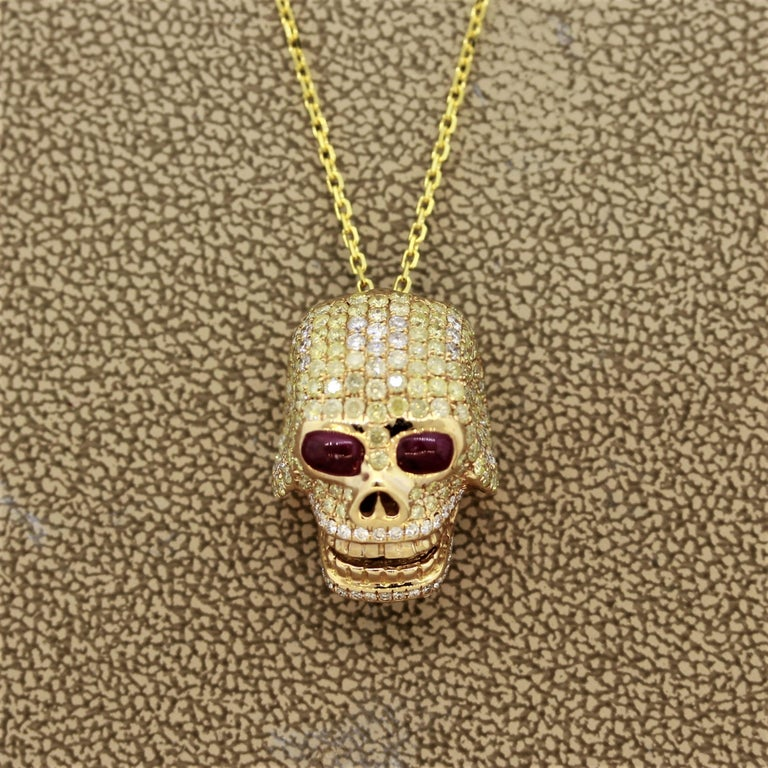 A gold skull pendant featuring 2.01 carats of round brilliant cut fancy colored diamonds. There are 2 ruby cabochons used as the eyes. Made in 18k yellow gold and comes with an 18k gold necklace.  Pendant Length: 0.75 inches  Necklace Length: 18