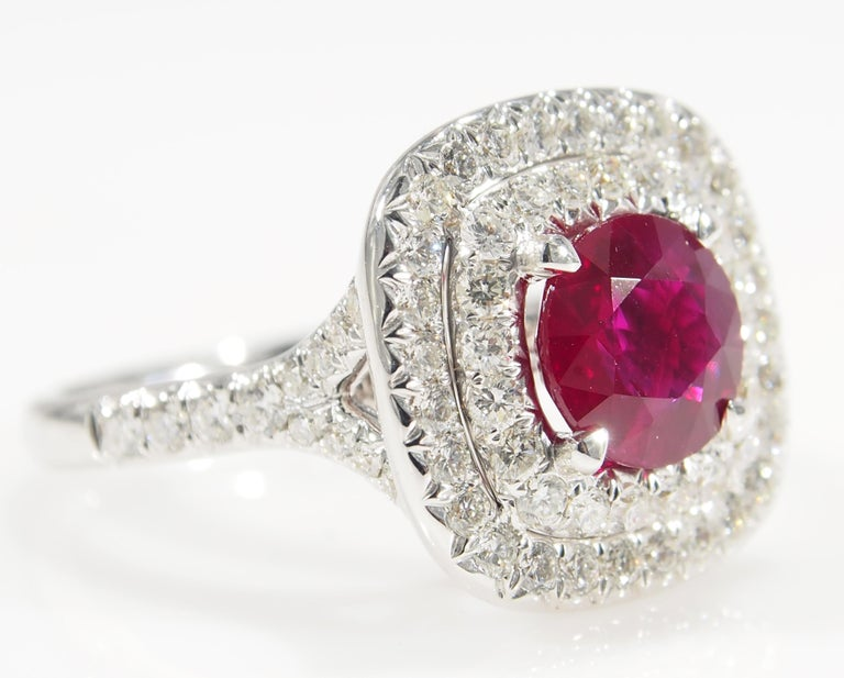 This is a classic 18K White Gold Diamond and Ruby Ring. There are (72) Round Brilliant Cut Diamonds set in a Double Halo and along the Shank for approximately 1.12ctw, G-H in Color, VS-SI in Clarity that accent the (1) Cushion Shape Ruby, 2.03ct. An