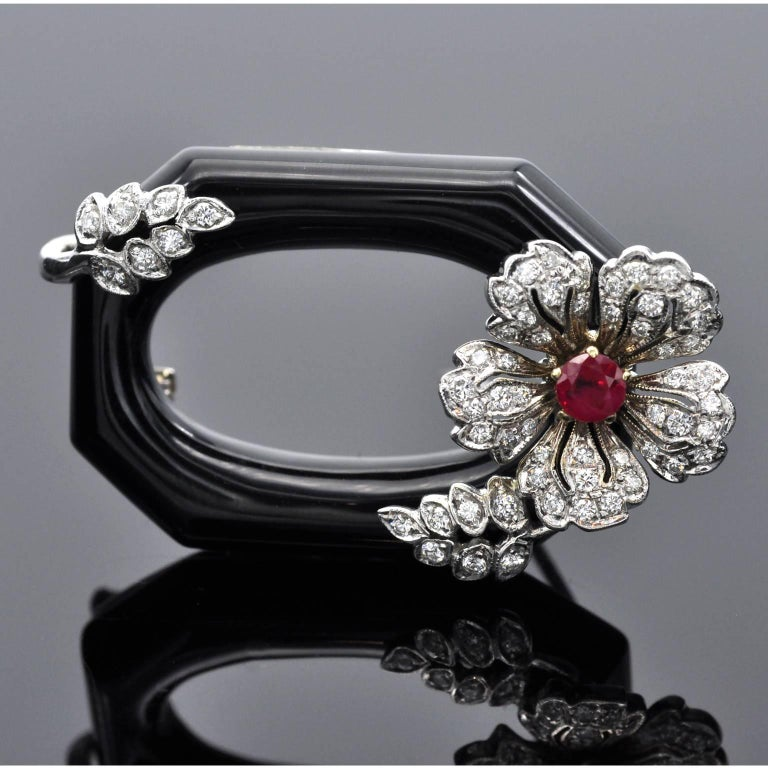 Exquisite Art Deco style Brooch. On a Onyx Hollolith a delicate 18 kt white gold flower set with diamond and in it center a round ruby. Item dertails: Diamonds: ± 0.45 carat Ruby: ± 0.25 carat Onyx: 4.5 carat: