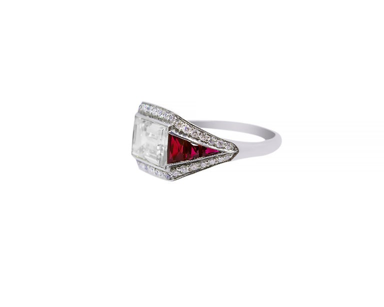 A beautiful cocktail ring decorated with a 2-carat emerald-cut diamond that's equivalent to K color, VVS2 clarity. The diamond is surrounded by tapered French-cut rubies and melee diamonds totaling to 1 carat.   The mounting is made in platinum