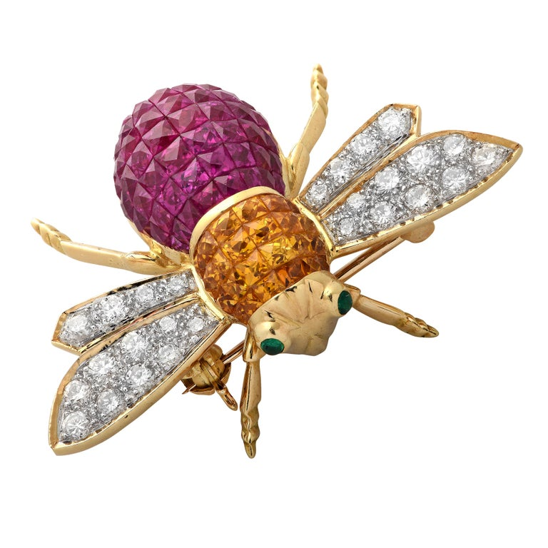 Delightful Bee Brooch Pin featuring an enchanting bee intricately crafted in 18 karat yellow gold. The body of the bee is encrusted with 60 round rubies weighing approximately 3 carats total, and 24 round yellow sapphires weighing approximately 1